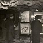 Vue de l'Exposition internationale du surréalisme, la salle principale. Des visiteurs admirent des œuvres placées sur des portes « revolver ».